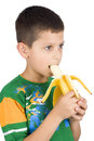 Menino que come a banana Fotografia de Stock Royalty Free