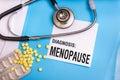 Menopause word written on medical blue folder