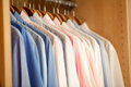 Mens blouses in a row of closet sorted by color Stock Photos