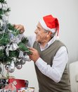 Mens die santa hat decorating christmas tree dragen Royalty-vrije Stock Afbeeldingen