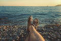 Mens legs in sneakers in background of picturesque sea landscape Summer Beach Relaxing Concept