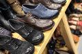 Mens shoes on the wooden shelves at a store Stock Photo
