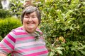 Mental disabled woman is showing a apple on a apple tree Royalty Free Stock Photo