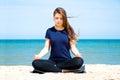 Mental health young woman practicing yoga at sea Stock Image