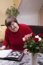 Mentally disabled woman looks at her collection of stamps Stock Image