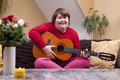 Mentally disabled woman playing guitar on a couch Royalty Free Stock Image