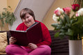 Mentally disabled woman is reading a book and smiles Stock Images