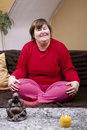 Mentally disabled woman sitting cross legged on the couch Royalty Free Stock Photography