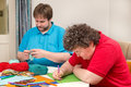 Mentally disabled woman and young man doing arts and crafts a women men Stock Photo
