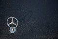 Mercedes Benz star logo stands up on wet car hood in morning dew Royalty Free Stock Photo