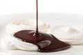Meringue with chocolate meringues on a white plate a stream of sauce being poured over Royalty Free Stock Images