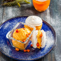 Meringue with ice cream of sea buckthorn on a blue plate on a dark wooden background Royalty Free Stock Photo