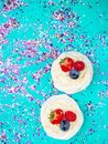 Meringue Pavlova with cream and fresh berries, strawberries, raspberries, blueberries on festive blue background with confetti, Royalty Free Stock Photo