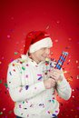Merriment portrait of joyful man in santa cap and white pullover having fun with confetti cracker Stock Photo