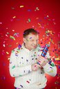 Merriment portrait of joyful man in white pullover having fun with confetti cracker Royalty Free Stock Images