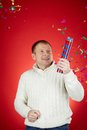 Merriment portrait of joyful man in white pullover having fun with confetti cracker Stock Photography