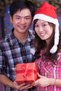 Merry chrismas young asian girl and boyfriend with a present box at Royalty Free Stock Image