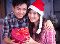 Merry chrismas young asian girl and boyfriend with a present box at Royalty Free Stock Photography