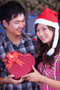 Merry chrismas young asian girl and boyfriend with a present box at Royalty Free Stock Images