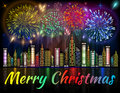 Merry Christmas banner decorated with fireworks exploding in night sky over downtown city Royalty Free Stock Photo