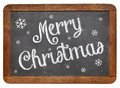 Merry christmas on blackboard white chalk text a vintage slate Stock Image
