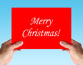 Merry christmas card in hands on blue background Stock Images