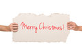 Merry christmas cardboard message script text as a on held by two hands isolated on white background concept Stock Images
