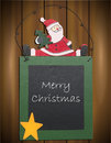 Merry christmas chalkboard with santa claus and text on wooden background Royalty Free Stock Photography
