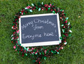 Merry christmas from everyone here message on a chalkboard festive greeting in handwriting with tinsel on green grass for office Royalty Free Stock Photos