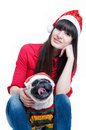 Merry christmas funny and cute friends � pretty girl and her pug dog pet � wearing red santa claus caps having fun smiling Royalty Free Stock Image