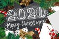 2020 Merry Christmas and Happy New Year banner with white list, fir branches, gifts, candy and confetti. Top view illustration.