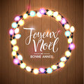 Merry Christmas and Happy New Year. French Language. Glowing Christmas Lights Wreath for Xmas Holiday Greeting Card Design. Wooden Royalty Free Stock Photo