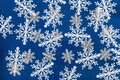 Merry Christmas and Happy New Year greeting card design with white  paper cut snowflakes on blue background. Seasonal holidays, Royalty Free Stock Photo