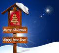 Merry christmas and happy new year wooden signboard with text a small wooden stylized tree sky snow Royalty Free Stock Images