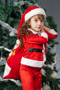 Merry christmas a little girl dressed in a suit snta claus standing near a tree and holding a red bag with gifts Stock Photo