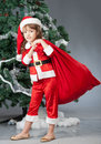 Merry christmas a little girl dressed in a suit snta claus standing near a tree and holding a red bag with gifts Stock Image