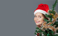 Merry christmas little girl in santa hat smiling and peeking out from behind the tree Stock Photo