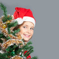 Merry christmas little girl in santa hat smiling and peeking out from behind the tree Royalty Free Stock Photography