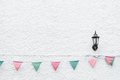 Merry Christmas Party flags bunting hanging on white wall background on x`mas eve holiday event. Minimal hipster style design. Royalty Free Stock Photo