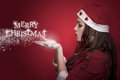 Merry christmas profile of a beautiful brunette in the santa costume blowing snowflakes and make words Royalty Free Stock Photo