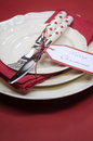 Merry christmas red theme individual table place settin setting with fine bone china plates and polka dot cutlery with gift tag Stock Photo