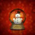 Merry christmas snow globe dome with snowman holding candy cane and inscription on red defocused background Stock Images