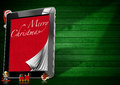 Merry christmas tablet computer with pages objects with red velvet and word marry on green wooden wall Stock Photos