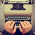 Merry christmas typewritten in a paper sheet on a typewriter wi young man typewriting the text an old with retro effect Royalty Free Stock Photo