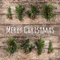 Merry Christmas Typographical on wooden background with fir branches, pine cones and snowflakes on wooden background. Xmas and New Royalty Free Stock Photo