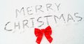 Merry christmas words written in snow hand with a red ribbon ideal for holiday greeting card design Royalty Free Stock Image