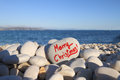 Merry christmas written on heart shaped stone on the beach with spray brush Royalty Free Stock Photo