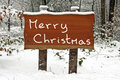 Merry Christmas written on a snowy wooden sign