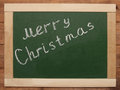 Merry christmass christmas handwritten with white chalk on a blackboard Royalty Free Stock Image