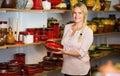 Merry female customer picking red glazed crockery Royalty Free Stock Photo